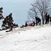 Kids sleding on the castle hillside.