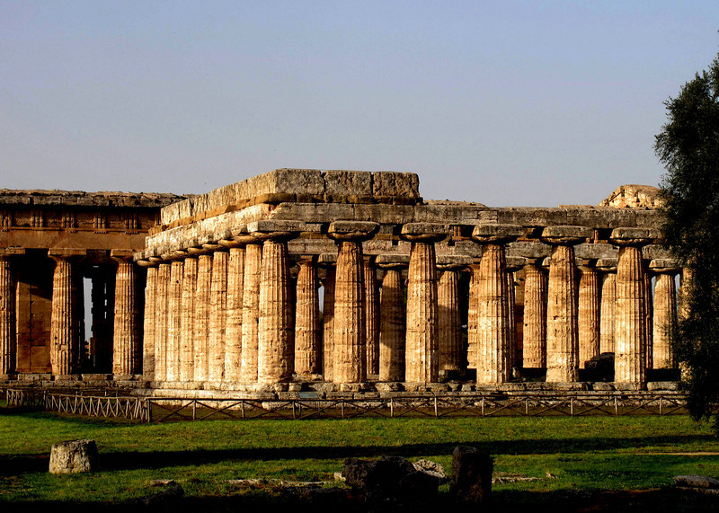 View of sunset at the Temples of Paestum. The main features of the site today are the standing remains of three major temples in Doric style, dating from the first half of the 6th century BC. These were dedicated to Hera and Athena, although they have traditionally been identified as a basilica and temples of Neptune and Ceres, owing to 18th-century mis-attribution.