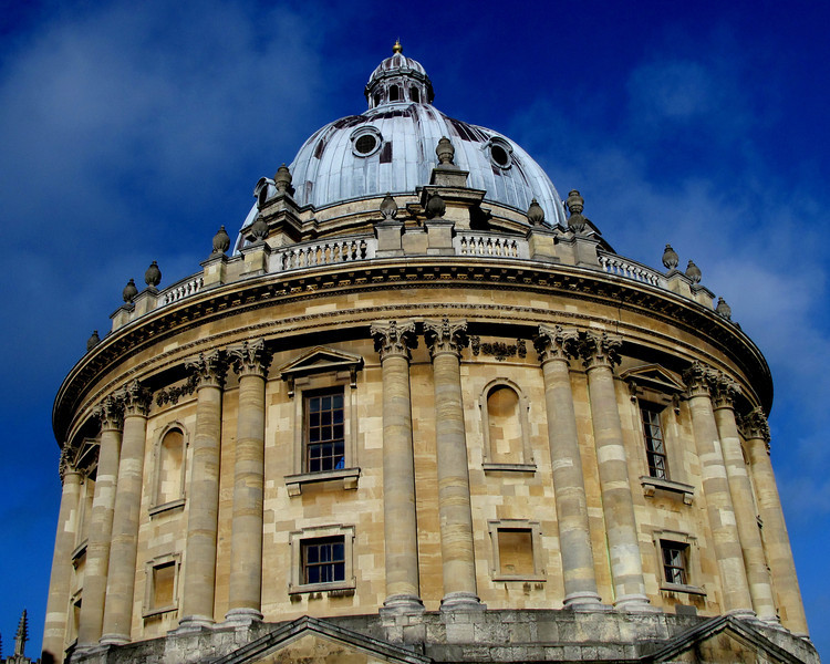 "Radcliffe Camera in Oxford on a beautiful Winter day January 2012.<br /> According to wiki ""The building is the earliest example in England of a circular library. It is built in three main stages externally and two stories internally, the upper one containing a gallery. The ground stage is heavily rusticated and has a series of eight pedimented projections alternating with niches. The central stage is divided into bays by coupled Corinthian columns supporting the continuous entablature. The pedimented windows stand above mezzanine openings, reflecting the interior arrangement. The top stage is a lanterned dome on an octagonal drum, with a balustraded parapet with vases.<br />  <br /> The construction used local stone from Headington and Burford, which was then ashlar faced. The dome and cupola are covered with lead. The original plan was for a stone dome, but after building 5 ft. 8 in. of the stonework, it had to be removed and the design was changed. Inside, the original walls and dome were distempered but this was later removed, revealing the decorations to be carved in stone. Only the decorative work of the dome is plaster"""