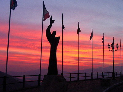 DELPHI, GREECE - We arrived in Delphi in time to see a beautiful sunset over the Gulf of Corinth.  At the end of the village's main street, an array of flags represent the countries that visited Greece during the Summer Olympics 2004.  The statue commemorates the eternal Olympic flame carried through the village on its way to Athens.