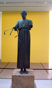 DELPHI, GREECE - The most famous artifact in the museum is the Charioteer, a bronze statue of a youth in a chariot race.  Originally, the figure stood in a bronze chariot drawn by two horses, but only pieces of the sculpture remain.