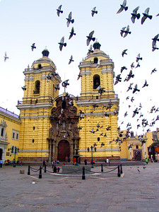 "LIMA, PERU - The ""jewel"" of colonial Lima is almost certainly the Monasterio de San Francisco.  Facing a small square full of pigeons, its extraordinary stone front is painted in the yellow ochre typical of the colonial period."