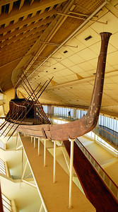 """THE PHARAOH'S SOLAR BARQUE - In the 1960s, the 1,224 pieces discovered in one of the boat pits were removed and carefully reassembled.  The result was a fully functional boat, now displayed in a specially constructed – and totally out-of-place – enclosure beside the Great Pyramid.   Made from Lebanese cedarwood, Khufu's boat is 142 feet long and 20 feet wide.  The boat was rowed by 10 pairs of oars, and two large steering oars are in the back.  Why bury boats in the dessert?  They were possibly """"solar barques,"""" meant to convey the dead pharaoh's """"sun spirit"""" across the sky each day.  Or perhaps to transport him to the afterworld.  The one in the museum shows some signs of having once been in the water, leading some to conclude that it was used to transport the dead pharaoh's body down the Nile from Memphis to Giza for burial."""