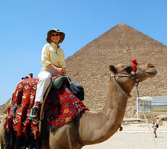 """TWO ICONS OF EGYPT - With the Great Pyramid as the backdrop, Jeanne couldn't resist the whole """"Egyptian Experience"""" - climbing onto her first camel for a brief jaunt (actually, very brief) over the desert sands of the Giza Plateau."""