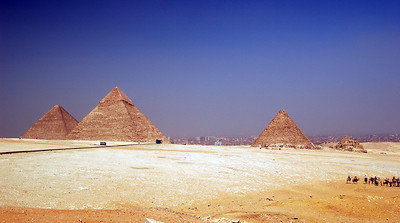 THE GIZA PLATEAU - A panorama of the pyramids at Giza. To the left is the Great Pyramid of Khufu, in the middle is the pyramid of Khafre and to the right is Menkaure's and his queens' pyramids. Note how the middle pyramid appears to be taller because it was built on a higher part of the plateau.