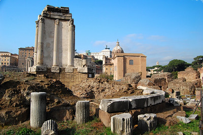 ANCIENT ROME - The Forum from behind the Temple of the Vesta.  The Temple's internal cella was surrounded by 20 Corinthian columns built on a podium. Another round outer wall went along the entire outside with more columns. The temple was modeled after the first Roman houses which were round huts made of mud and straw.