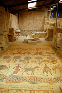 """MOUNT NEBO - Inside the chapel in what is called the """"Old Baptistry,"""" we found the most interesting of the mosaics.  Four rows of human and animal figures (bears, ostriches, lions, and in the lower right, either a spotted camel or a strange looking giraffe) have led scholars to a variety of interpretations.  No one really knows the true meaning of the mosaic, which was found when another mosaic on top was removed.  Researchers now believe there is yet another mosaic beneath this one."""