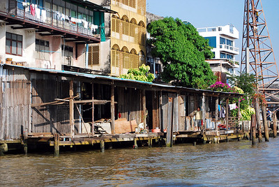 "BANGKOK - A boat trip along the Chao Phraya is one of Bangkok's most delightful activities.  Admidst modern buildings are still small stilt houses that spill into the river, vestiges of ""old Bangkok."""