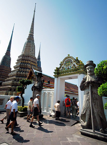 BANGKOK - Guarding the gates to the inner courtyard are huge stone figures bedecked with top hats.