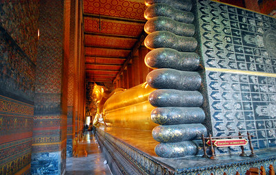 BANGKOK - The Reclining Buddha is 150 feet (46 meters) long and 50 feet (15 meters) high.  The soles of its feet are encrusted with mother-of-pearl inlays that describe the 108 signs that identify an enlightened one.