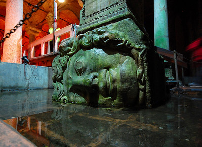 """ISTANBUL - The Basilica Cistern is an amazing - and eerily strange - place on its own, but adding to its strangeness are two ancient stone heads that the Byzantine engineers """"recycled"""" to use as bases for two of the columns.  They didn't seem to pay much attention to their orientation."""