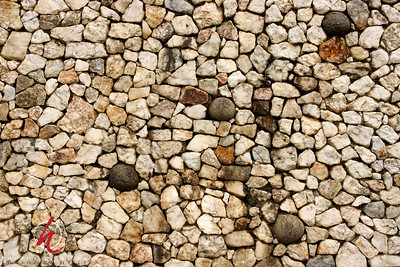 """Quartz wall rebuilt in 1970's using original stones from area. """"Egg"""" shaped stones represent cycle of life here at New Grange."""