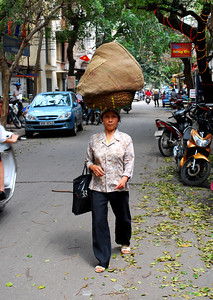 The Vietnamese seem to manage walking on the streets with no problems - even with heavy burdens.   Why walk in the streets?  Sidewalks are impassable - they are too valuable as parking lots for motorcycles.
