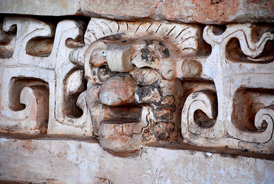 Angels or demons?   This rather homely face protruding from the facade was probably carved in homage to one of the Maya's gods, illustrating the strange fact that the Maya often portrayed their dieties with less-than-flattering appearances.