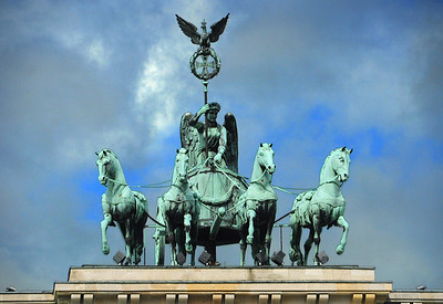 """Atop the gate is the Quadriga, the triumphal statue of a winged goddess driving a four-horse chariot, added in 1793.  In 1806 when Napoleon defeated Prussia and triumphantly entered its capital through the gate, he ordered the Quadriga shipped to Paris. The emperor thus became known locally as the """"horse thief of Berlin.""""  Upon his defeat in 1814, a triumphant procession returned the Quadriga to Berlin."""