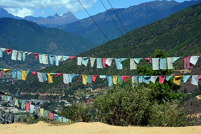 Power lines crisscross Buddhist prayer flags.  Only in the decade of the 60s was the country's first electricity generated.