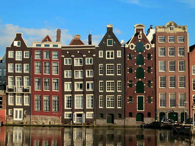 """Much of Amsterdam was once a swamp, so many the early houses of the city's early bankers and merchants were built on wooden pilings.  Over time, the pilings began to wobble and sink, and the houses began to tilt.  The Dutch – never ones to be concerned over something as trivial as off-kilter buildings – call these the """"Dancing Houses."""""""