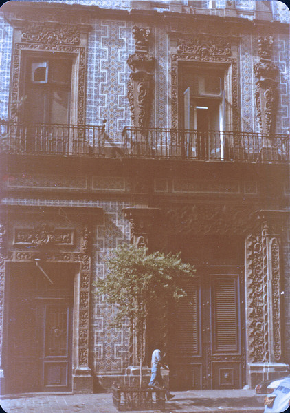 "House of Tiles from 1596 - Mexico City - May 1979<br /> There are two conflicting explanations of how this building got its current appearance. The more reliable version states that the fifth Countess Del Valle de Orizaba, who resided in Puebla, decided to return to the capital after her husband's death and remodeled the house with Puebla tile in 1737, to show the family's immense wealth.[1][4][5] The other version is more colorful and tells of a son whose lifestyle caused his father to state that if he didn't change his ways he would ""never build his house of tiles,"" meaning that he would never amount to anything. As an act of defiance, the young man had the tiles put on when he inherited the house. These tiles cover the three exposed facades of the house on both levels."