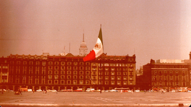 Zocalo Plaza de la Constitucion - Mexico City - May 1979<br /> The central feature of Mexico City is the Zócalo (Plaza de la Constitución), where Mexico's first Constitution was proclaimed in 1813. Measuring some  780 ft (240 m) each way, it is one of the largest squares in the world. The Spaniards began to lay out the square immediately after the conquest of Tenochtitlán, with its northern half overlying the southern part of the demolished Aztec temple precinct, the Teocalli. In the early colonial period the square served a variety of purposes. Today the square is one large empty space, which is used for festivals, parades and demonstrations. A huge flag is hoisted every morning. Dominating the square are the National Palace and the Cathedral.<br /> <br /> Latino-Americana Tower in the background is 44 stories and rests on floating piles sunk into clay.
