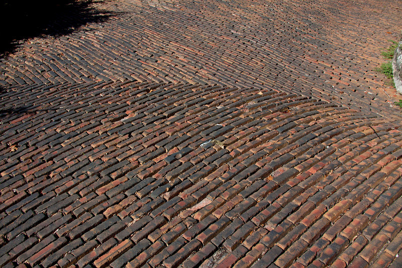 The bricks are tilted toward the top of the hill to give horses' hooves better grip.