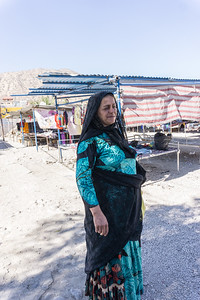 On the road.  A nomadic woman selling clothing along the road.