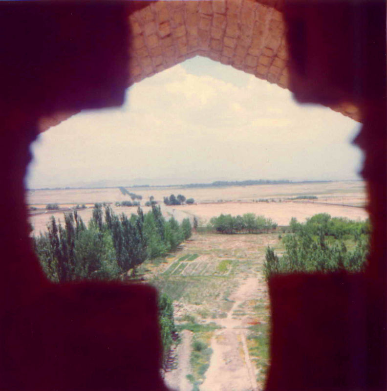 looking out at the land through a cross-shaped window.