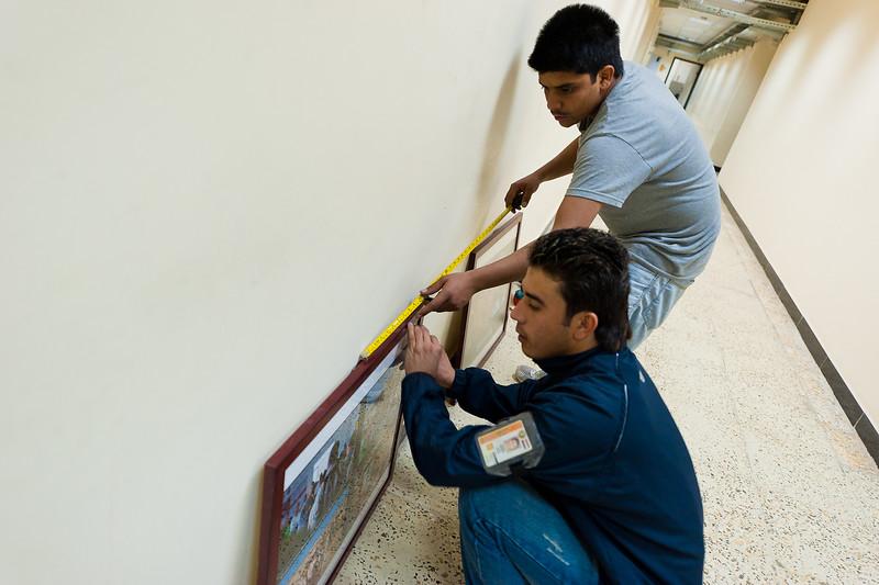 3 DEC 2011 - Almco workers hang framed photos inside BLDG One at FOB Union III, Baghdad, Iraq.  Photo by John D. Helms - john.helms@iraq.centcom.mil.