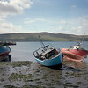 Dingle Harbor at low tide. This effect of small boats keeled over is thanks to the more extreme tides seen in Britain in general.