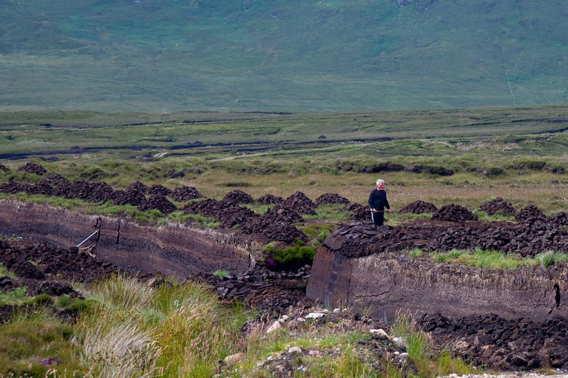 """We had asked Matthew about peat bogs and turf bogs and the difference between them.  He stopped the bus at this turf bog to give us a closer look.  This is the """"unhappy camper"""" who ran toward us yelling and screaming and waving his bog tool at us to clear off!"""