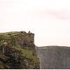 Foolhardy pilgrims tempting fate at cliff's edge.
