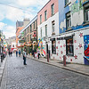 Few people walking in narrow quaint cobbled street in Temple Bar area with shop signage  and street art on both sides