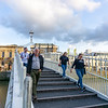 People croossing on the pedestrian  Ha'penny Bridge across Liffey River in city