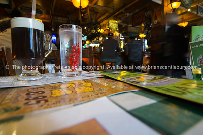 two glasses on table containing water with red berries and Guinness Stout
