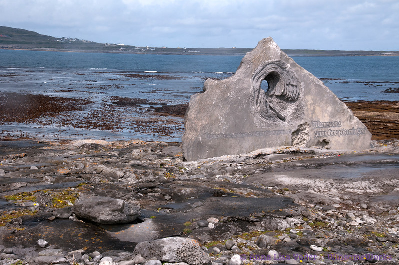 """Carved memorial stone completed in 2013 during the Festival of Stone (Feile na gCloch). Found just meters away, it was transformed into a tribute to those lost at sea in the Aran Isles. It depicts a currach (Irish vessel) engulfed by waves. """"Maireann a gcuimhne fos i m' aigne"""" (We will always remember them in our minds.)"""