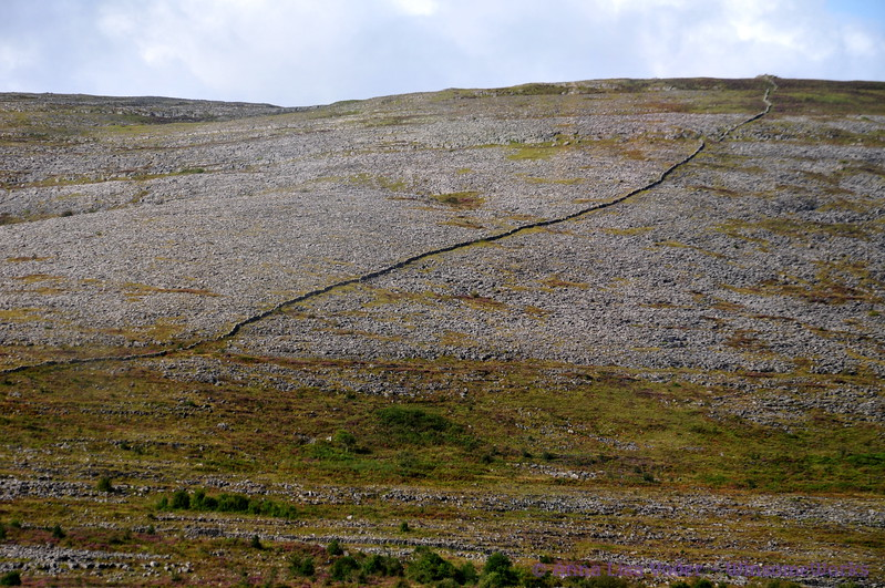 The Burren near West coast of Ireland, with ancient stone fence running all the way up