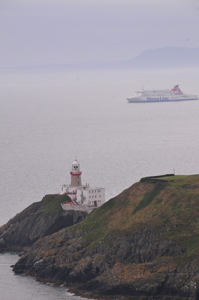 Baily lighthouse with ship in Irish Sea