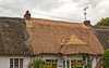 Here re-thatching of a roof is in progress---a costly proposition.