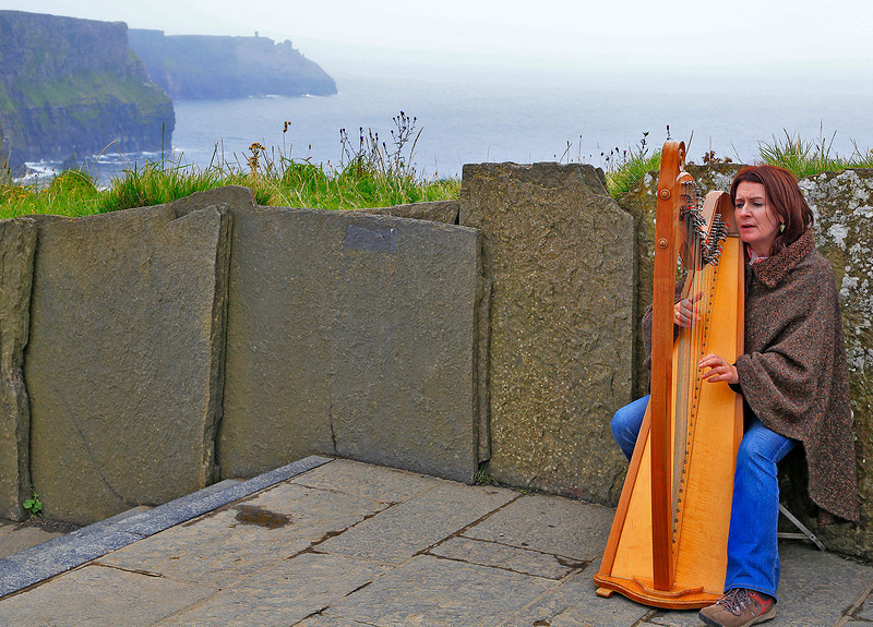 Well known Irish harpist and ballad singer Tina Mulrooney playing at the Cliffs of Moher.