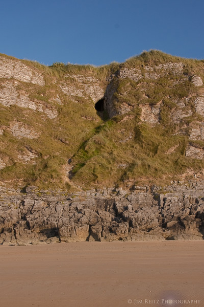 "The ""Goat's Hole' in the cliff below Tralee #18 ntee box, seen from the beach."