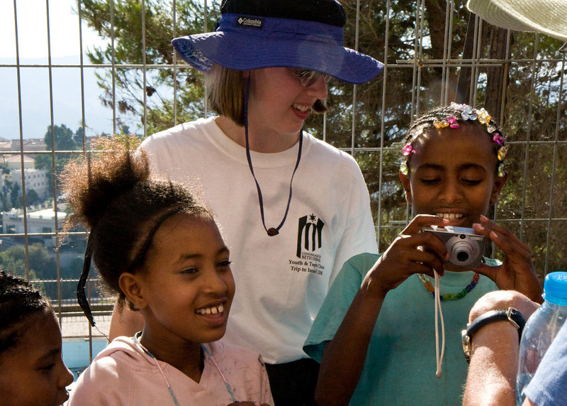 After the singing, the real connections were made showing digital photos to the kids. Becca shows some girls how to work the camera