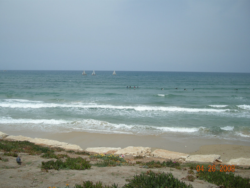 Surfers and sailboat at Tel Aviv Beach