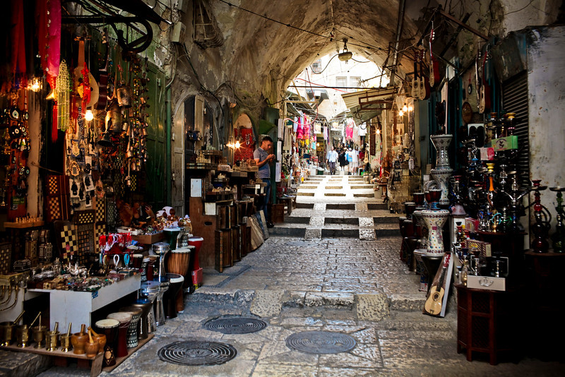 "The Arab Quarter in Old Jerusalem.  Many winding, narrow streets mostly filled with sidewalk shops like this one.  PS - you are looking at the ""street"" itself ascending through that archway."