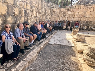 The group seated on ancient marble toilet seats in Beth Shean