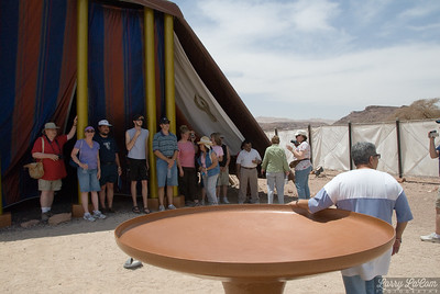 Our guide is resting her arm on the bronze laver, with some of our group assembled in the shade of the tent of meeting.