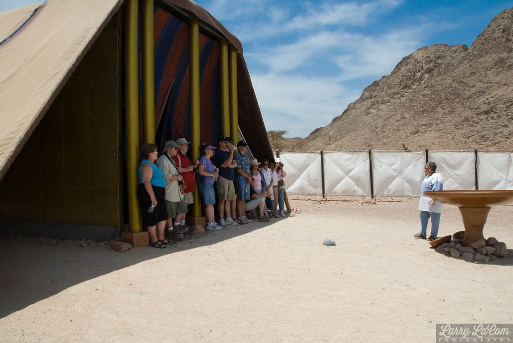Our guide standing next to the bronze laver with some of our group assembled in & The Tabernacle at Timna - LaComStudio