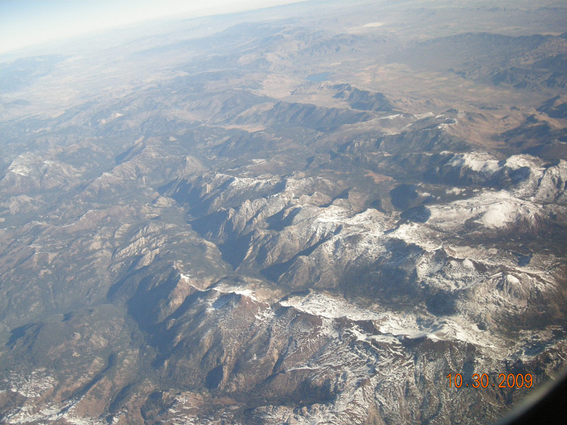 As seen from plane, snow capped mountains.... May be Sierra Nevada, CA???