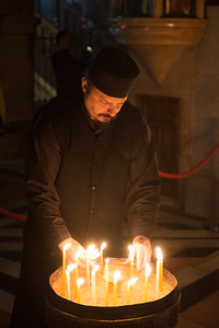 tending to the candles at the site of the crucifixion.