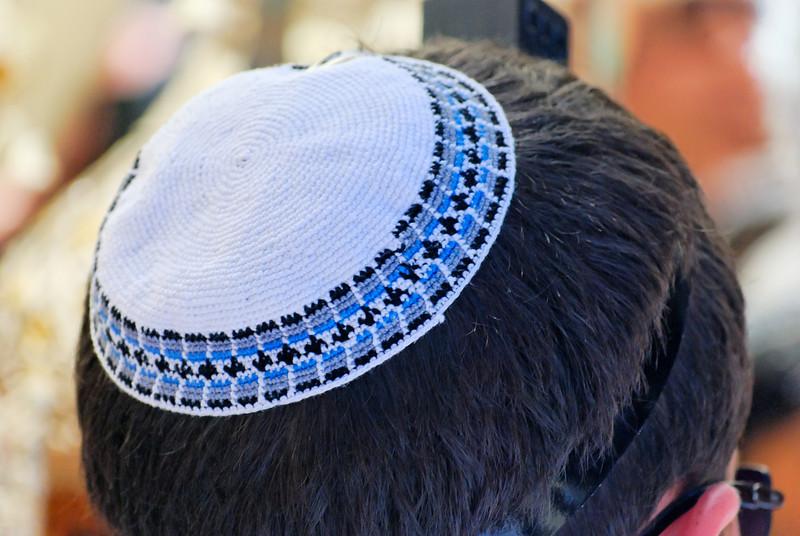 """A quipá (em hebraico כיפה, kipá, """"cúpula"""", """"abóbada"""" ou """"arco"""") ou yarmulke (em iídiche יאַרמלקע, yarmlke, do polonês jarmułka, que significa """"boina""""), é um pequeno chapéu em forma de circunferência, semelhante ao solidéu, utilizada pelos judeus tanto como símbolo da religião como símbolo de """"temor a Deus"""".<br /> Quipás (kipót)à venda em Jerusalém<br /> O Talmude enfatiza a necessidade de se ter sempre o temor a Deus sobre nossas cabeças. A maioria dos judeus utiliza a quipá apenas em ocasiões solenes e de devoção, enquanto alguns utilizam-no o dia inteiro, ilustrando a necessidade de se temer a Deus em todos os momentos da vida.<br /> O surgimento da quipá e o sentido inicial do seu uso dentro do judaísmo até hoje não tem uma explicação satisfatória. No entanto, durante muito tempo seu uso não foi obrigatório. Somente no século XIX, diante do perigo da assimilação, os ortodoxos instituíram a obrigatoriedade do uso. Certas ramificações, como os caraítas, não seguem esse costume.<br /> De acordo com a tradição, apenas homens devem usar quipá, ainda que nos tempos modernos ramificações não-ortodoxas do judaísmo permitam que as mulheres também a utilizem. Seu uso é usualmente associado ao reconhecimento da superioridade divina sobre o ser humano, sendo o símbolo de humildade perante o criador e de submissão à sua vontade."""