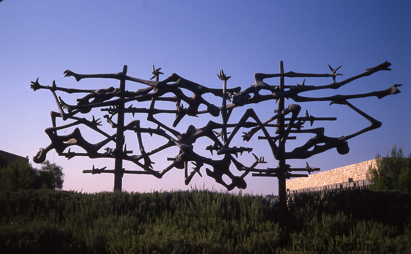 """Yad Vashem Memorial Sculpture:<br /> """"In Memory of the Victims of Concentration Camps,"""" Jerusalem, between 1987 and 1989. This smaller replica of Nandor Glid's Dachau memorial was installed at Yad Vashem in 1979. The bronze sculpture, with its explicit reference to the European graphic tradition of crucifixions and pietàs, interacts differently with the landscape and sunlight of Jerusalem than with its setting at Dachau. (Source: Sybil Milton, In Fitting Memory.)"""