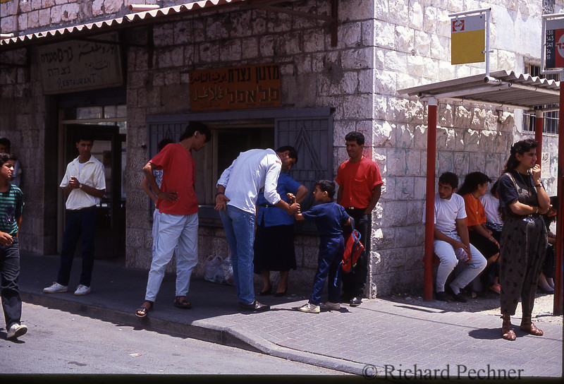 Young boy getting reprimanded by an adult on the sidewalk in the West Bank.